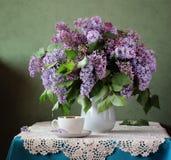 Ramo de lila y de taza Aún vida rústica con las flores Imagen de archivo libre de regalías