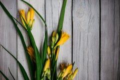 ramo de lirios amarillos en un fondo de madera, casandose el ramo imagen de archivo