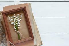 Ramo de lirios del valle en un marco de madera en una pila de libros viejos fotos de archivo