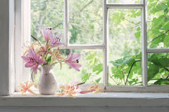 Ramo de los lirios en travesaño de la ventana en un día soleado Fotos de archivo libres de regalías