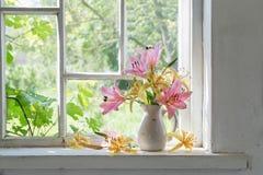 Ramo de los lirios en travesaño de la ventana en un día soleado Imagenes de archivo