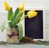 Ramo de los tulipanes con la pizarra en blanco Fotos de archivo libres de regalías