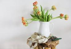 Ramo de los tulipanes en el florero blanco en silla rústica de madera Imagen de archivo