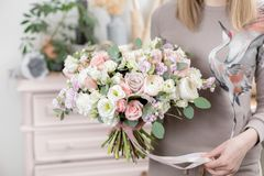 Ramo de lujo hermoso de flores mezcladas en mano de la mujer el trabajo del florista en una floristería muchacha preciosa linda imagen de archivo