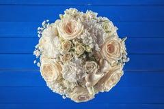 Ramo de marfil de la boda de rosas en el fondo de madera azul, arreglo floral en el color en colores pastel, celebración Foto de archivo libre de regalías