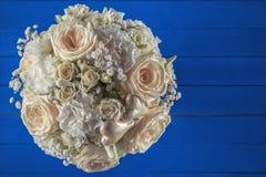 Ramo de marfil de la boda de rosas en el fondo de madera azul, arreglo floral en el color en colores pastel, celebración Imágenes de archivo libres de regalías