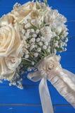 Ramo de marfil de la boda de rosas en el fondo de madera azul, arreglo floral en el color en colores pastel, celebración Imagen de archivo libre de regalías