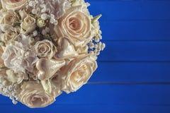 Ramo de marfil de la boda de rosas en el fondo de madera azul, arreglo floral en el color en colores pastel, celebración Fotos de archivo libres de regalías