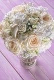 Ramo de marfil de la boda de rosas en el fondo de madera rosado, arreglo floral en el color en colores pastel, celebración Fotos de archivo