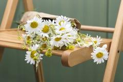 Ramo de margaritas que mienten en una silla de madera Fotos de archivo