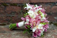 Ramo de orquídeas, de rosas, de iris y de otras flores en un fondo natural Foto de archivo
