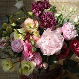 Ramo de peon?as del rosa, amarillas y p?rpuras en un florero imagen de archivo