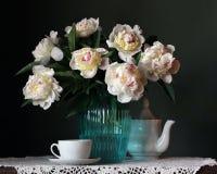 Ramo de peonías en un florero y un juego de té Imagen de archivo libre de regalías