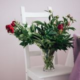 ramo de peonías rojas en un florero en la silla blanca, casandose la decoración fotografía de archivo