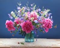 Ramo de peonías rosadas y de otras flores en un florero de cristal en Foto de archivo