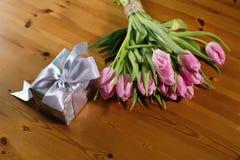Ramo de rosa de los tulipanes en un fondo y un regalo de madera hermosos Foto de archivo
