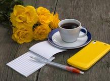 Ramo de rosas amarillas, de teléfono, de cuaderno y de café Fotografía de archivo