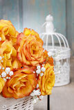 Ramo de rosas anaranjadas en una cesta de mimbre y un vintage blancos bir Fotos de archivo
