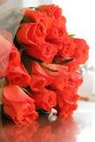 Ramo de rosas anaranjadas en una tabla de madera con la reflexión imagen de archivo