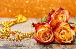 Ramo de rosas anaranjadas y rojas en la tabla de madera Fotografía de archivo