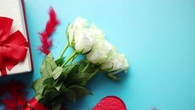 Ramo de rosas blancas con el arco rojo en fondo azul Regalo encajonado en lado