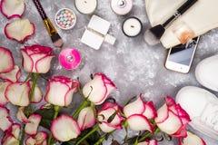 Ramo de rosas con los cosméticos en perfume, teléfono y zapatillas de deporte en un fondo gris con el espacio de la copia Foto de archivo libre de regalías