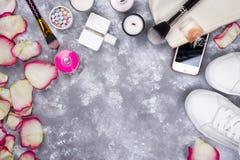 Ramo de rosas con los cosméticos en perfume, teléfono y zapatillas de deporte en un fondo gris con el espacio de la copia Imagenes de archivo