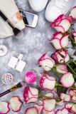 Ramo de rosas con los cosméticos en perfume, teléfono y zapatillas de deporte en un fondo gris con el espacio de la copia Fotografía de archivo libre de regalías