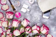 Ramo de rosas con los cosméticos en perfume en un fondo gris con el espacio de la copia Foto de archivo libre de regalías
