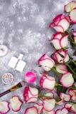 Ramo de rosas con los cosméticos en perfume en un fondo gris con el espacio de la copia Fotografía de archivo