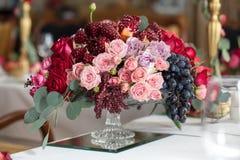 Ramo de rosas, de peonías, de uvas y de granadas en el estilo holandés Imagenes de archivo