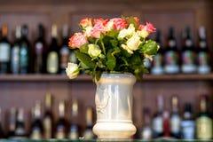 Ramo de rosas en un contador de cerámica blanco del florero contra el estante de botellas Imagenes de archivo