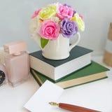 Ramo de rosas en un florero, pila de libros, tarjeta con la pluma de la montaña en la tabla delante del fondo blanco fotos de archivo