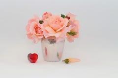 Ramo de rosas en un florero y un corazón Foto de archivo