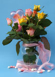 Ramo de rosas multicoloras en un florero con la cinta rosada Fotos de archivo libres de regalías