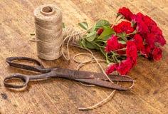 Ramo de rosas rojas, bola de la guita y viejo Rusty Scissors en el Wo fotos de archivo