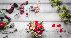 Ramo de rosas rojas, de corazones, de calas, de claveles y de cintas en la tabla Foto de archivo