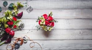 Ramo de rosas rojas, de corazones, de calas, de claveles y de cintas en la tabla Fotos de archivo libres de regalías