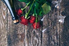 Ramo de rosas rojas, dos vidrios, botella del vino, caja de regalo con la etiqueta en el tablero de madera del vintage Rose roja  Fotos de archivo