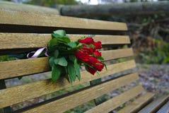 Ramo de rosas rojas en banco imagenes de archivo