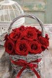 Ramo de rosas rojas en cesta de mimbre Imagen de archivo libre de regalías