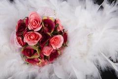 Ramo de rosas rojas en la pluma blanca Imágenes de archivo libres de regalías