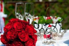 Ramo de rosas rojas en un fondo de los accesorios de la boda Foto de archivo
