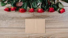 Ramo de rosas rojas en una tabla de madera con un sobre y una tarjeta de papel en blanco para su texto Imagen de archivo libre de regalías