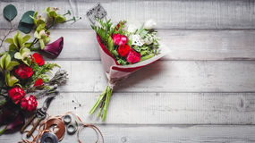 Ramo de rosas rojas y blancas, de corazones, de calas, de claveles y de cintas en la tabla Fotos de archivo libres de regalías