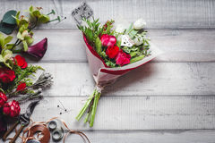 Ramo de rosas rojas y blancas, de corazones, de calas, de claveles y de cintas en la tabla Fotos de archivo