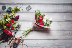 Ramo de rosas rojas y blancas, de corazones, de calas, de claveles y de cintas en la tabla Imagenes de archivo