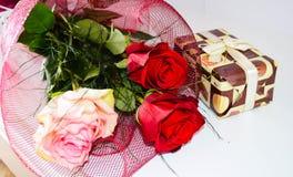 Ramo de rosas rojas y de presente en un fondo blanco Imagen de archivo libre de regalías