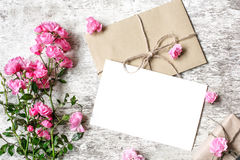 Ramo de rosas rosadas blandas con una tarjeta de felicitación en blanco Imagen de archivo