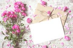 Ramo de rosas rosadas con la tarjeta y los pétalos de felicitación alrededor Foto de archivo